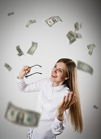 exult: Rejoicing. Woman in white and falling dollar banknotes. Success, currency and lottery concept. Stock Photo