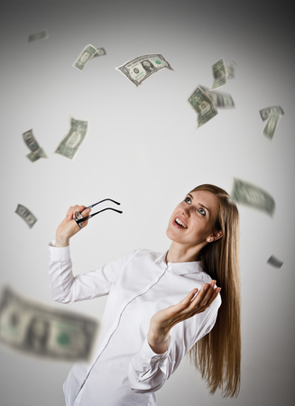 Rejoicing. Woman in white and falling dollar banknotes. Success, currency and lottery concept. Stock Photo