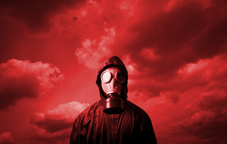 gasmask: Man wearing a gas mask on his face. Gas mask and red sky.
