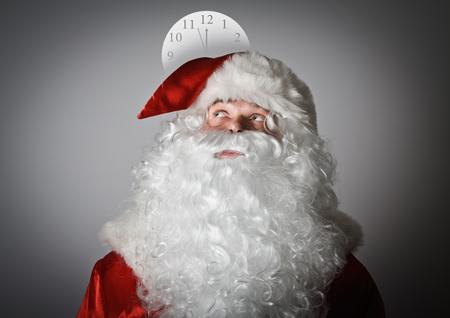 Santa Claus and clock above head. photo