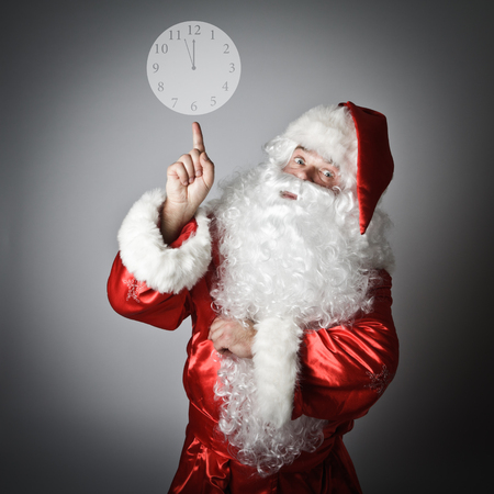 Santa Claus is pointing at the clock on grey background.