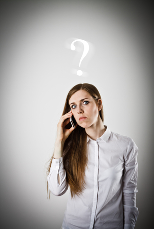 despite: Woman in white is using a mobile phone. Question concept. Stock Photo