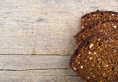 Slices of whole grain brown bread on wooden table. Reklamní fotografie