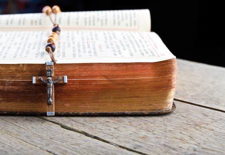 The book of Catholic Church liturgy and rosary beads on the wooden table Stock Photo