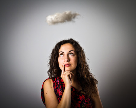 Girl and cloud. Imagination concept. Young woman is doing something.