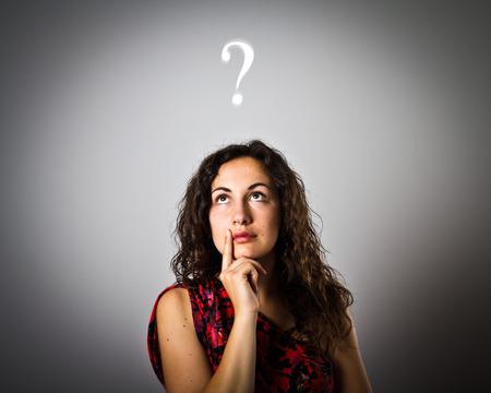 Meisje is vol twijfels en aarzeling. Meisje en vraagteken boven het hoofd. Jonge vrouw is iets aan het doen.