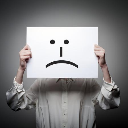 Frau hält Weißbuch mit Lächeln. Unglückliches und Problemkonzept. Standard-Bild - 87482540