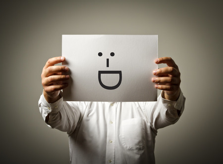 subconsciousness: Man is holding white paper with smile. Laughing and smiling concept. Stock Photo