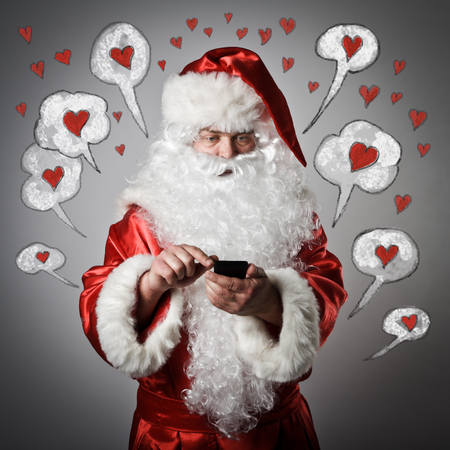 Santa Claus is using a mobile phone. Love concept.