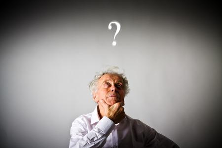 Oude man is vol twijfels en aarzeling. Oude man en vraagteken boven het hoofd.