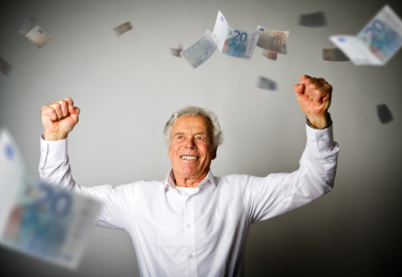 Happy old man in white and falling Euro banknotes. Currency and lottery concept.