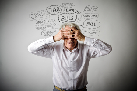 Frustrated old man in white. Taxes, debts and other problems. Stock fotó