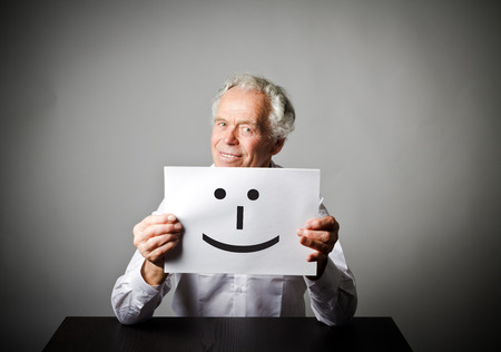 Old man in white is holding white paper with smile. Happy and smile concept