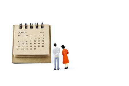 August. Two thousand eighteen year calendar and two miniature plastic figures. Man and woman on white background. Planning for the future – marriage, wedding or pregnancy.
