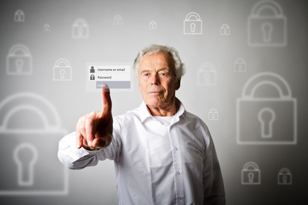 Old man in white is pushing the virtual button. Login and password concept. Stock Photo