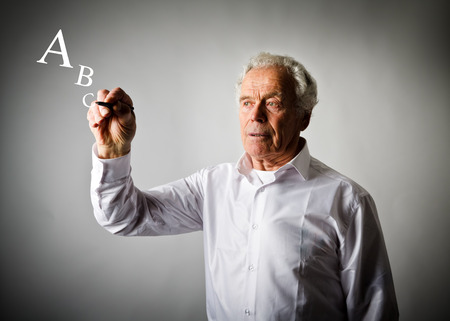 Old man in white is writing something. Old man in white and letters. Alphabet.