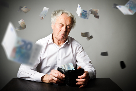 Worried old man in white is looking at a twenty euro and wallet. Accounting and taxes concept. Stock Photo