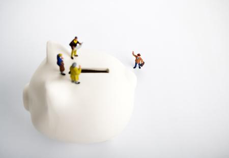 Businessman figurines on a piggybank. Money, business, corruption and expectation concept.