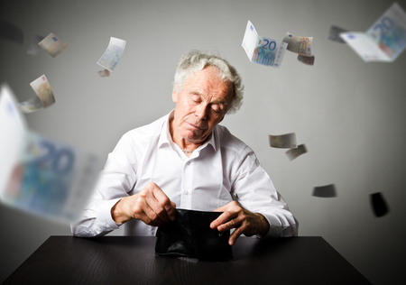 Old man in white and empty wallet. Accounting and taxes concept.