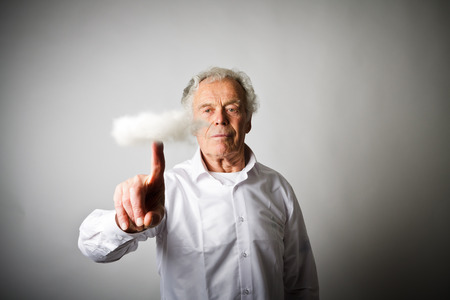 Old man in white is pushing the virtual cloud. Imagination and virtual cloud concept.