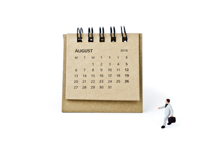 August. Meeting in August. Two thousand eighteen year calendar and miniature plastic businessman on white background. Datebook and travel concept.