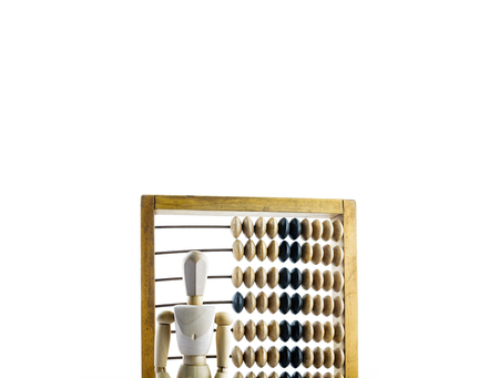 Wooden mannequin with wooden calculator on bright background. Wooden abacus.