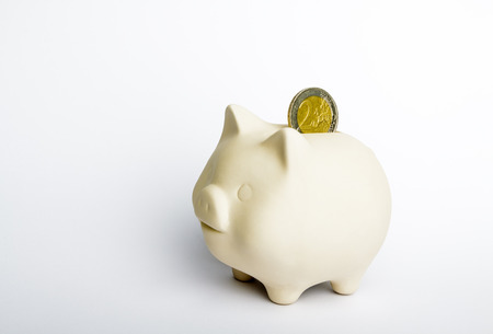Piggy bank and two euro coin on bright background. Saving and economy concept. 写真素材