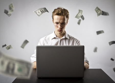 Young man using a laptop to browse the net. Young worker and falling dollar banknotes. Currency and job concept. Banco de Imagens - 121626943