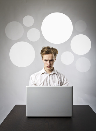 Young man using a laptop to browse the net. Man in white and gray bubbles. Stock Photo
