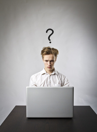 Young man using a laptop to browse the net. Question and trouble concept.