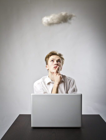 Young man in white with laptop and small cloud. Imagination and virtual cloud concept.