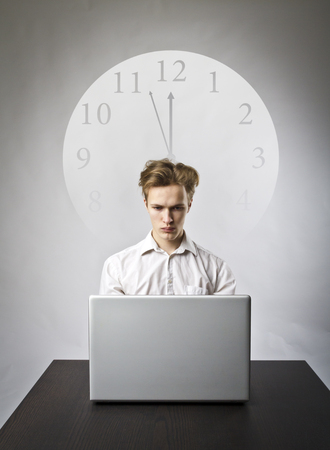 Young man using a laptop to browse the net. Man in white and clock. Three Minutes to Twelve. Time is passing. 스톡 콘텐츠