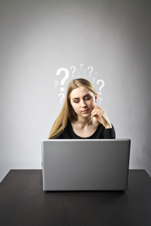 Young woman using a laptop to browse the net. Questions, ignorance and trouble concept.