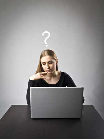 Young woman using a laptop to browse the net. Question, ignorance and trouble concept.
