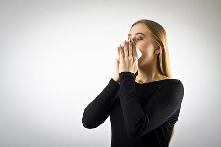 Mujer joven en negro está estornudando. Concepto de estornudo y alergia. Foto de archivo