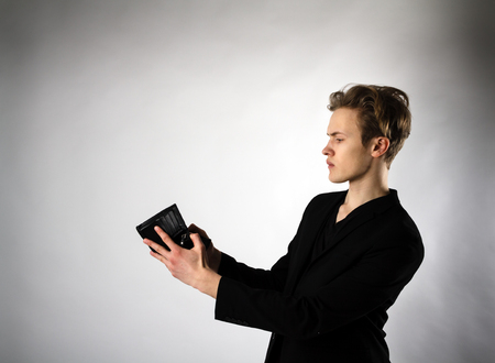 Worried young man is looking at an empty wallet.
