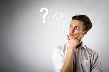 Le jeune homme est plein de doutes et d'hésitations. Jeune homme et points d'interrogation. Concept de doute et d'hésitation.
