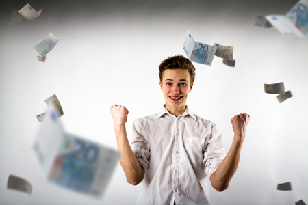 Young man in white is rejoicing. Success and happiness concept. Man in white and Euro. Banco de Imagens - 119947378