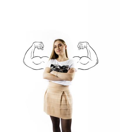 Giovane e forte donna in bianco. Concetto di donna forte. Donna abbastanza giovane con le braccia abbozzate forti e muscolose.