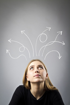 Frustrated young woman and arrows over her head. Expressions, feelings and moods. Woman solving a problem.