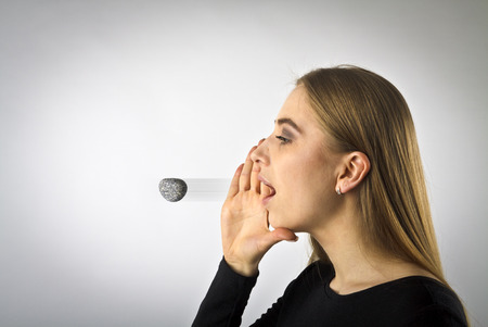 Woman in black is screaming at something. Word like a stone in motion - offensive word. A word spoken is past recalling. Stock Photo