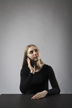 Jeune femme en noir au téléphone