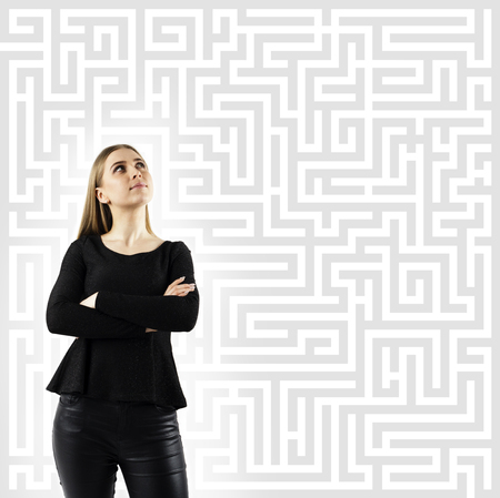 Maze. Young woman in black full of doubts and hesitation. Young woman looking for the solution. Girl solving a problem.