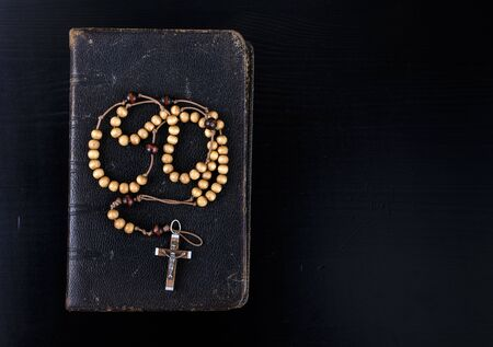 Rosary beads and prayer book. Rosary and book of Catholic Church liturgy on dark background. Banco de Imagens