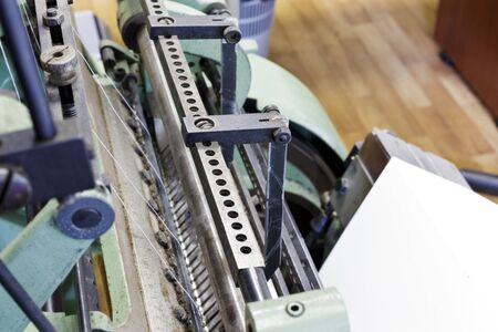 Machine for stitching book pages with threads in typography. Elements of the machine.