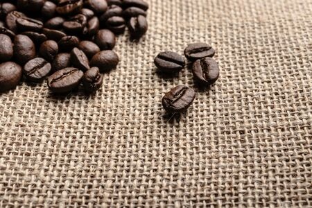 Coffee beans on burlap background. Macro. Reklamní fotografie