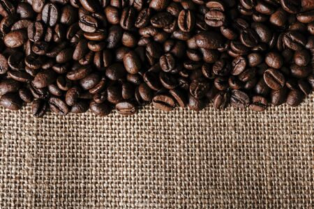 Coffee beans on burlap background. Macro.