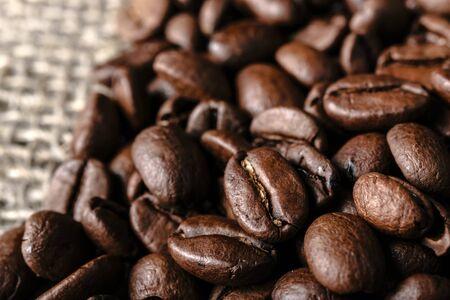 Coffee beans on burlap background. Macro.