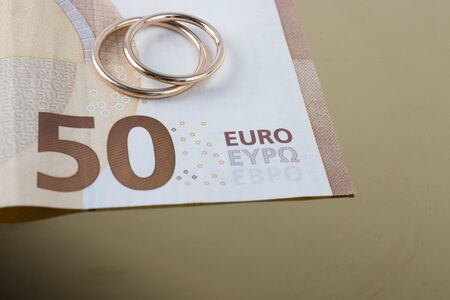 Two wedding rings and currency. Wedding rings and fifty euro. Wedding or divorce concept. Wedding Planning concept. Expenses.