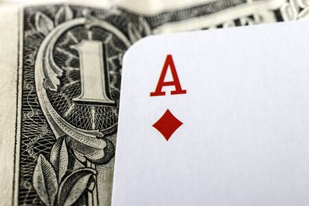 Ace of diamonds, playing card close up lying on top of United States Currency. Gambling, winning concept. Gambling entertainment. Play games of chance for money.